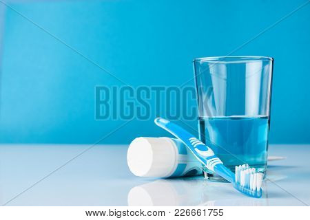 A Blue Toothbrush With Toothpaste And Glass Of Blue Mouthwash On Blue Background With Copy Space, Cl