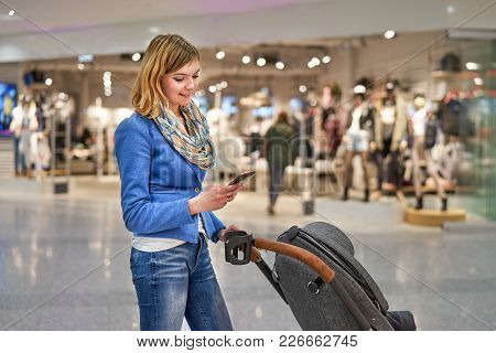 Young Beautiful Woman Staying With Pram In Front Of Clothing Store And Looking Into Mobile Phone
