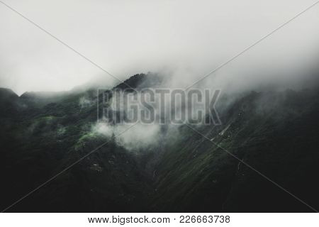 Low lying cloud and fog rolling in on a mountain in a sombre dark rainy alpine landscape obscuring the landscape