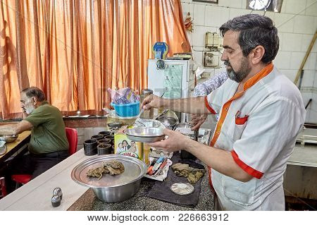 Tehran, Iran - April 28, 2017: An Elderly Iranian Chef At A Cheap Cafe Is Preparing Food.