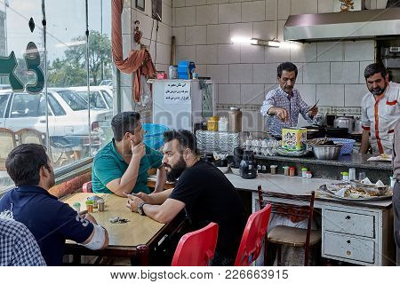 Tehran, Iran - April 28, 2017: Iranian Men Sit At A Table In A Small Cafe And Wait For Food.
