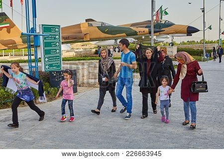 Tehran, Iran - April 28, 2017: Iranian Women In Hijabs, Man And Children Are Walking Around Holy Def