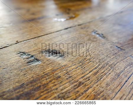 Wood grain and chip mark (indents) patterns on a hardwood table top. Closeup view. poster