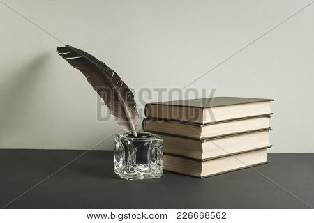 Stack Of Books And Quill Pen With Inkwell On The Table. Free Copy Space. Education Concept.