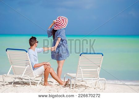 Young Couple On White Beach During Summer Vacation. Happy Lovers Enjoy Their Honeymoon At Exotic Isl