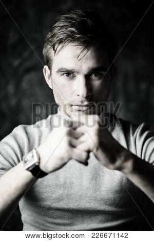 Portrait of a serious young man ready to strike. Man's strength and health.