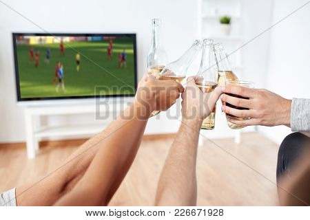 friendship, leisure and people concept - happy friends or soccer fans clinking non-alcoholic beer bottles and watching football game on tv at home