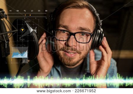 music, show business, people and voice concept - male singer with headphones singing to microphone at sound recording studio