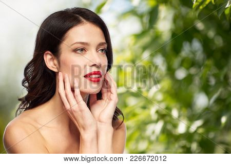 beauty, make up and people concept - happy smiling young woman with red lipstick over green natural background touching her face