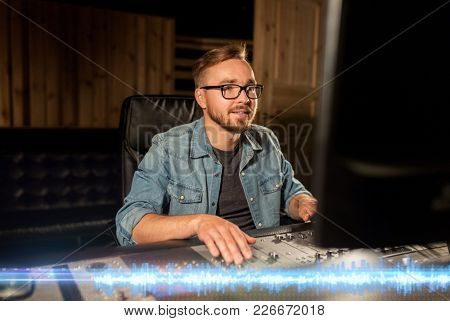 music, technology and people concept - man at mixing console in sound recording studio