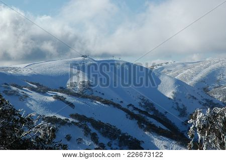 The Top Of A Snow-covered Mountain. A Ski-lift Runs Up The Mountainside And Along The Horizon. Tiny