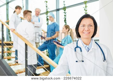 Team of doctors and senior woman as chief physician with competence