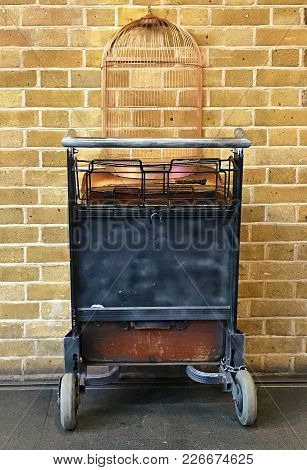 Close Up Of A Trolley With An Empty Bird Cage Against A Brick Wall At Kings Cross Station.