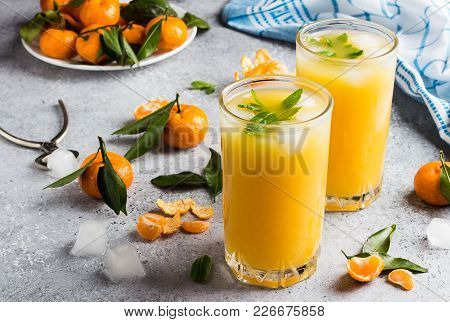 Tangerine Juice In Glasses On Light Background. Orange Mandarins Sweet Fresh Citrus Fruit Healthy Fo
