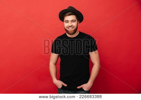 Portrait of handsome stylish man wearing black t-shirt and hat smiling on camera and posing with hands in pockets isolated over red background