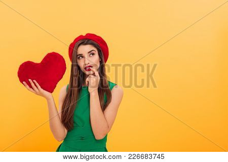 Image of thoughtful young woman standing isolated over yellow background holding heart. Looking aside.