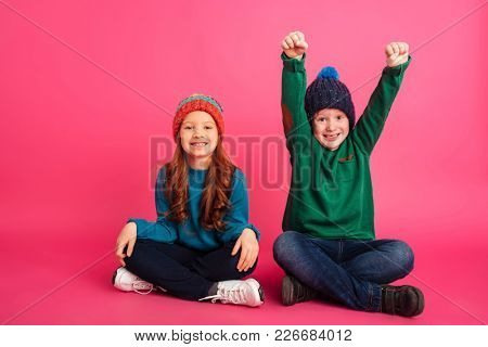 Happy ginger brother in green sweater sitting with pretty smiling sister and making winner gesture isolated