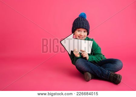 Smiling ginger boyin knitted hat and sweater holding arrow left and looking camera isolated over pink