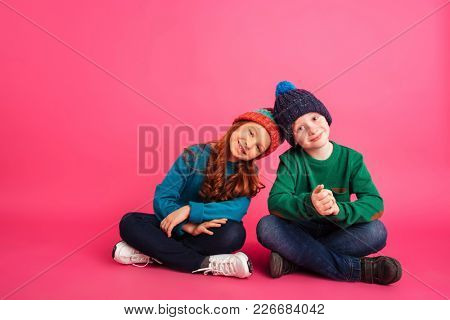 Cheerful girl and her ginger brother in colour clothes sitting on floor and smiling to camera isolated