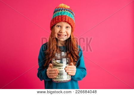 Cheerful ginger girl holding money box and smiling to camera isolated over pink