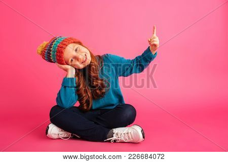 Cheerful redhead girl in colour hat pointing up at copy space and smiling to camera isolated