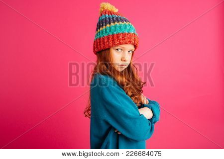 Upset ginger girl in coloured hat looking camera and and holding hands folded isolated