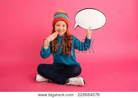 Smiling redhead girl looking to camera and holding blank bubble speech while sitting on floor isolated