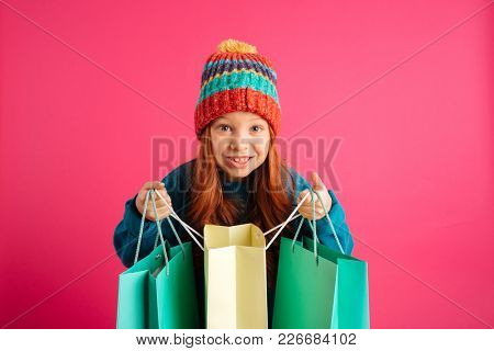 Happy beautiful girl in hat holding shopping bags and looking camera isolated over pink