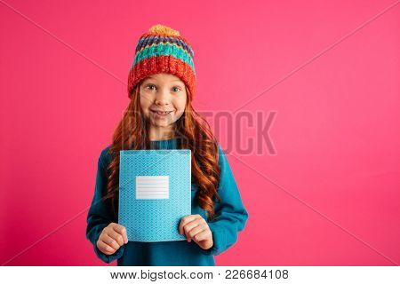 Young beautiful redhead girl showing blue copy book and smiling isolated over pink