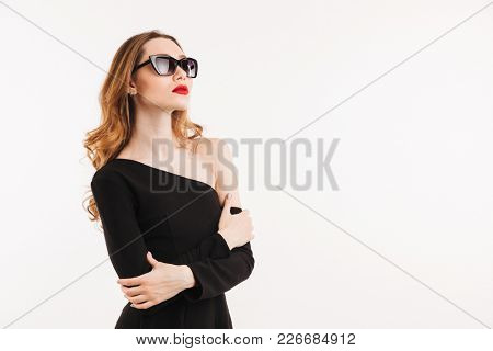 Portrait of a confident young woman dressed in black dress and sunglasses posing while standing and looking away at copy space isolated over white background