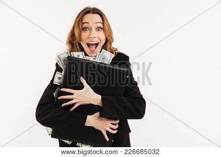 Portrait of an excited young businesswoman dressed in suit holding briefcase full of cash isolated over white background
