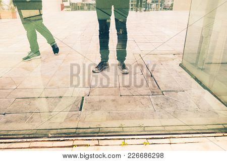 Low Section Of Two People Standing Reflected On Glass