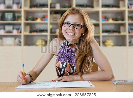 Beautiful Girl Smiling While Sitting At A Table And Writes