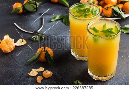 Tangerine Juice In Glasses On Dark Background. Orange Mandarins Sweet Fresh Citrus Fruit Healthy Foo