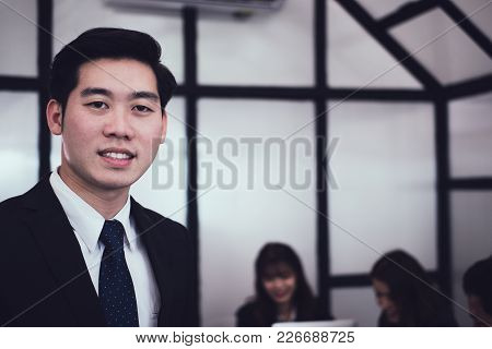Asian Businessman Smiling At Camera While Colleagues Have Meeting At Office. Business People Working