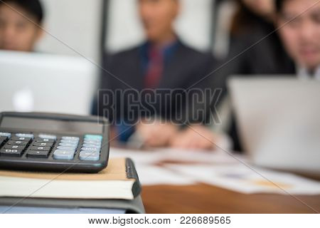 Calculator On Office Desk & Business People Having A Meeting. Businessman & Businesswoman Working Wi