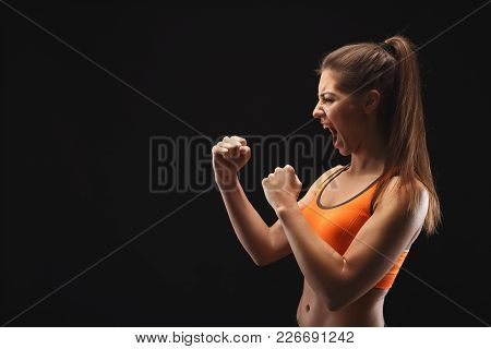 Emotional Female Fighter Ready To Fight Over Black Background. Kickboxing And Fight Sport Concept. S