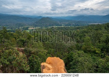 The Cliff Of Orange Soil Mountain In The Forest With Cloudy Sky View, Traveling In Thailand