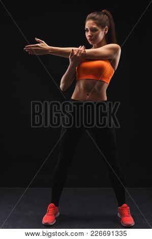 Athletic Female Fitness Model Showing Muscular Body, Preparing For Training. Studio Shot On Black Ba