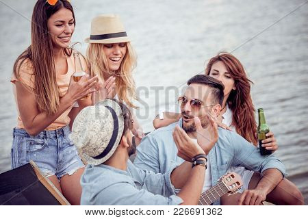 Group Of Friends Relaxing On The Beach Party.