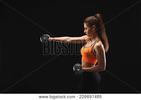Athletic Young Woman With Dumbbells Preparing For Fight On A Black Background. Studio Shot, Low Key,
