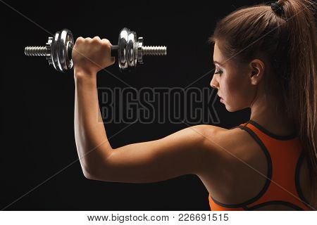 Athletic Young Woman With Dumbbell On A Black Background. Studio Shot, Low Key, Back View, Copy Spac