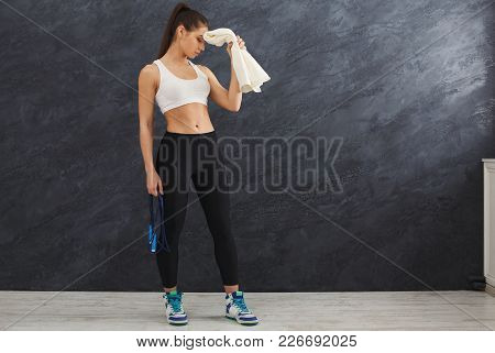 Beautiful Young Sport Woman With Towel After Training. Confident Fitness Girl Holding Skipping Rope
