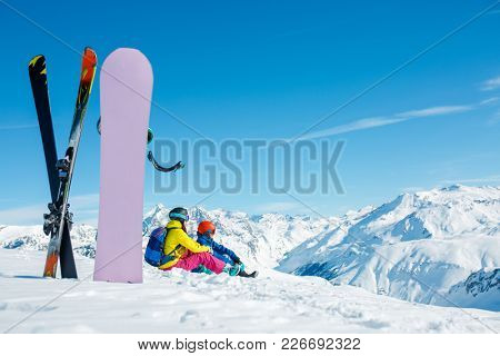 Picture of snowboard, skis on background of sitting sports couple on a snowy hill
