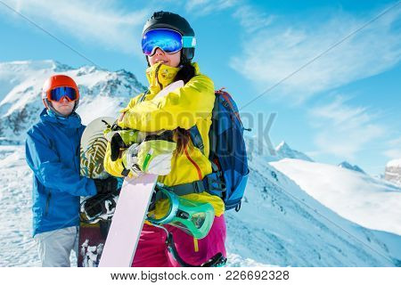 Image of sportive man and woman with snowboard against background of snowy hills