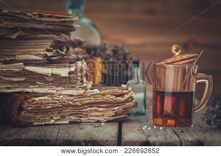 Old Books, Tincture Or Healthy Tea In Glass, Vial Of Homeopathic Globules And Medicinal Herbs.