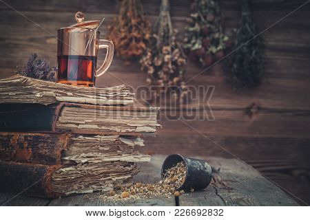 Cup Of Healthy Tea Or Tincture, Mortar Of Healthy Daisy Herbs And Stack Of Old Books. Hanging Bunche