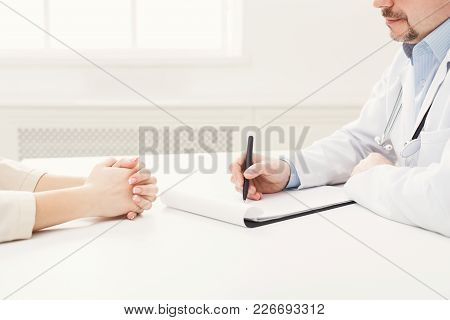 Closeup Of Patient And Doctor Taking Notes In Hospital. Doctor Consulting Woman, Healthcare And Medi