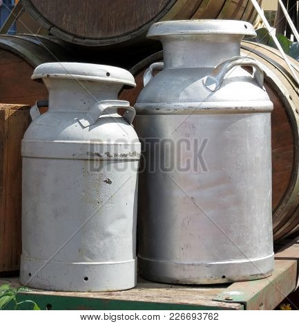 Aluminum Milk Cans Transported On An Old Wagon With Wooden Barrels.