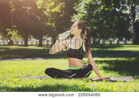 Exhausted Woman Wearing Sportswear Drinking Water After Training Outdoors While Sitting On The Mat.